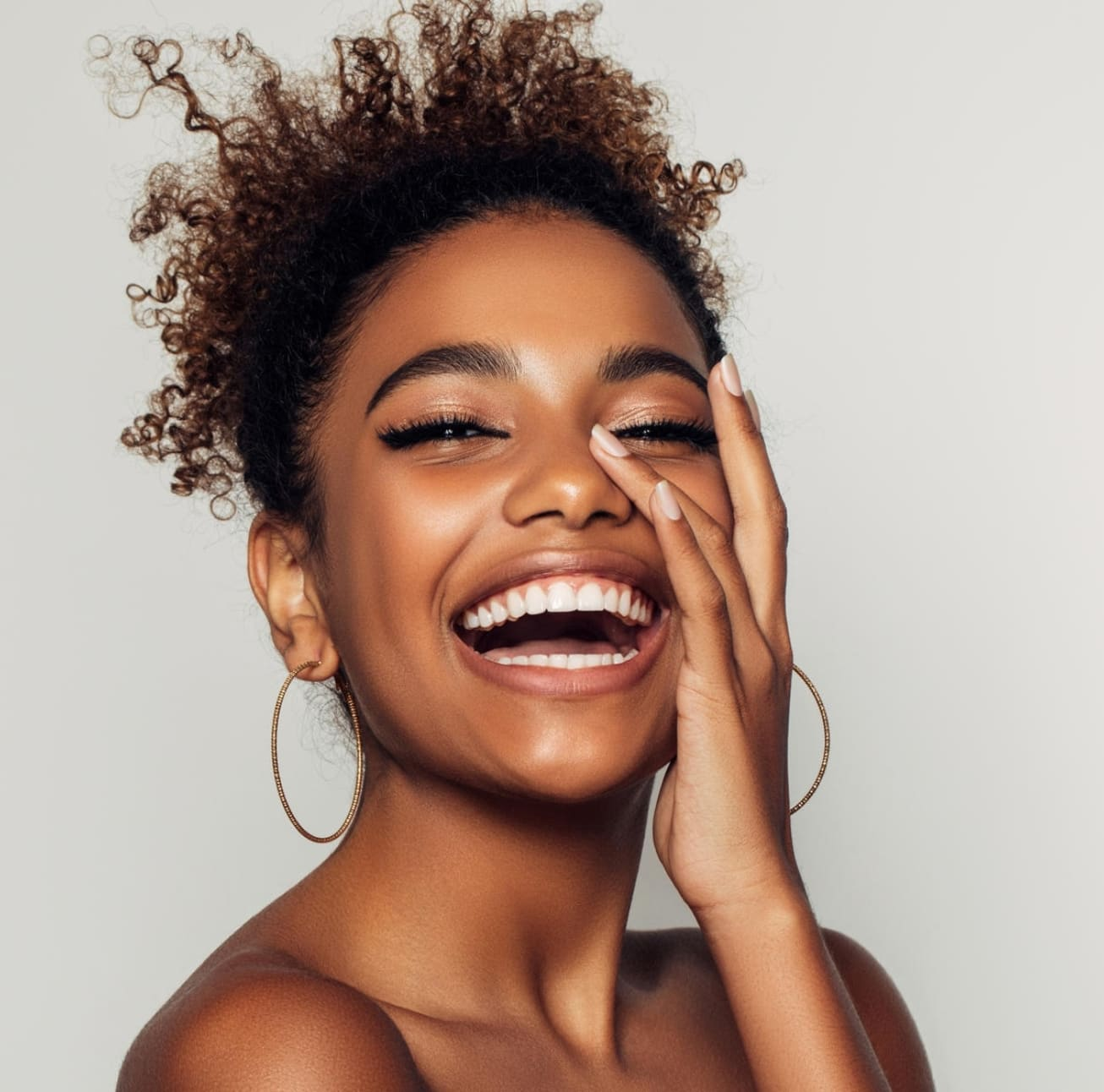 Laughing woman with great skin touching her face