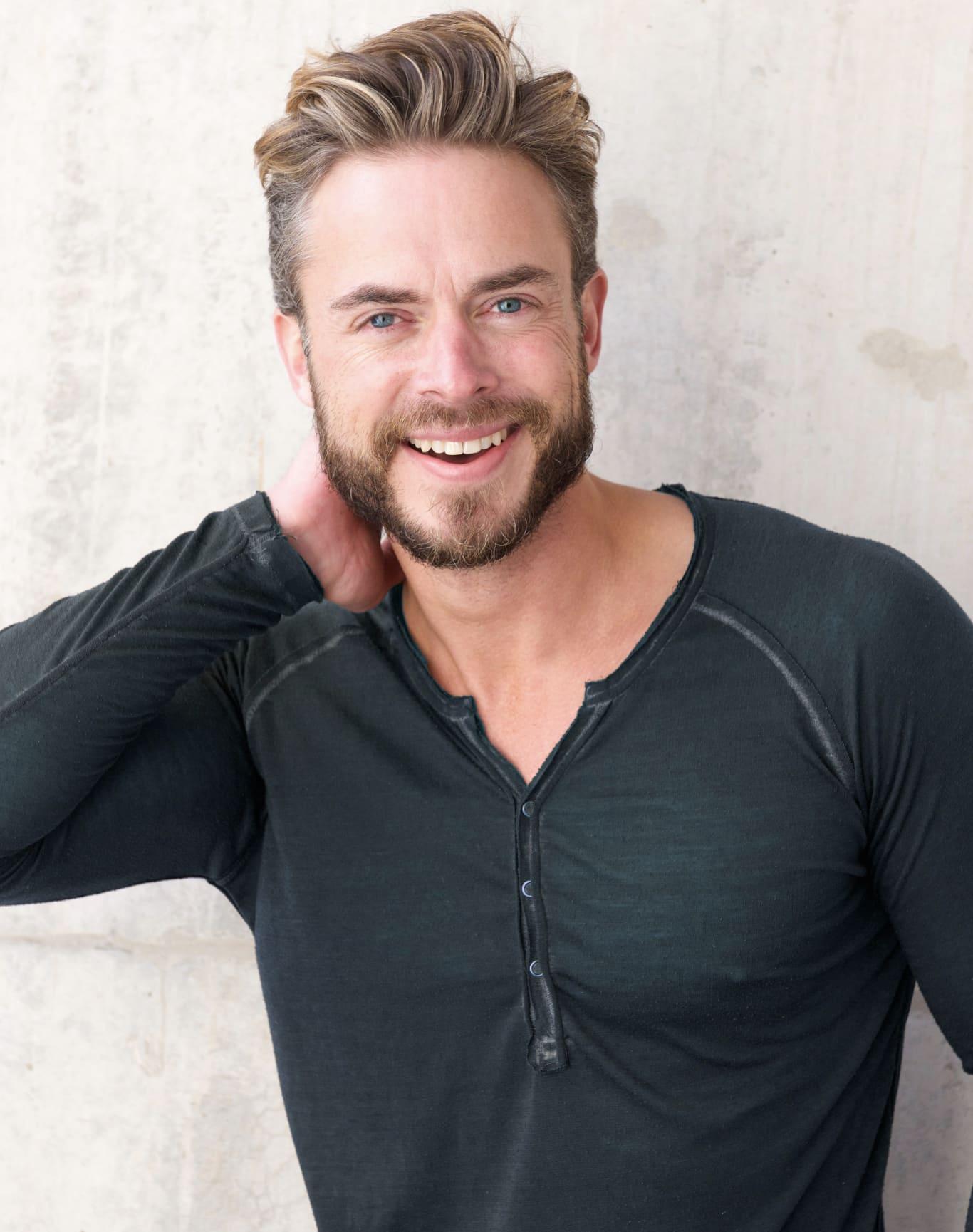 Smiling man wearing a black henley shirt