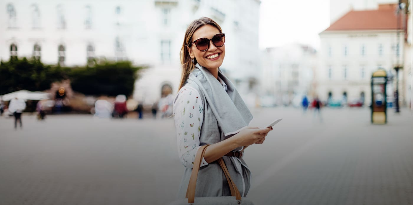 Fashionable woman wearing sunglasses and a gray scarf outside in the city