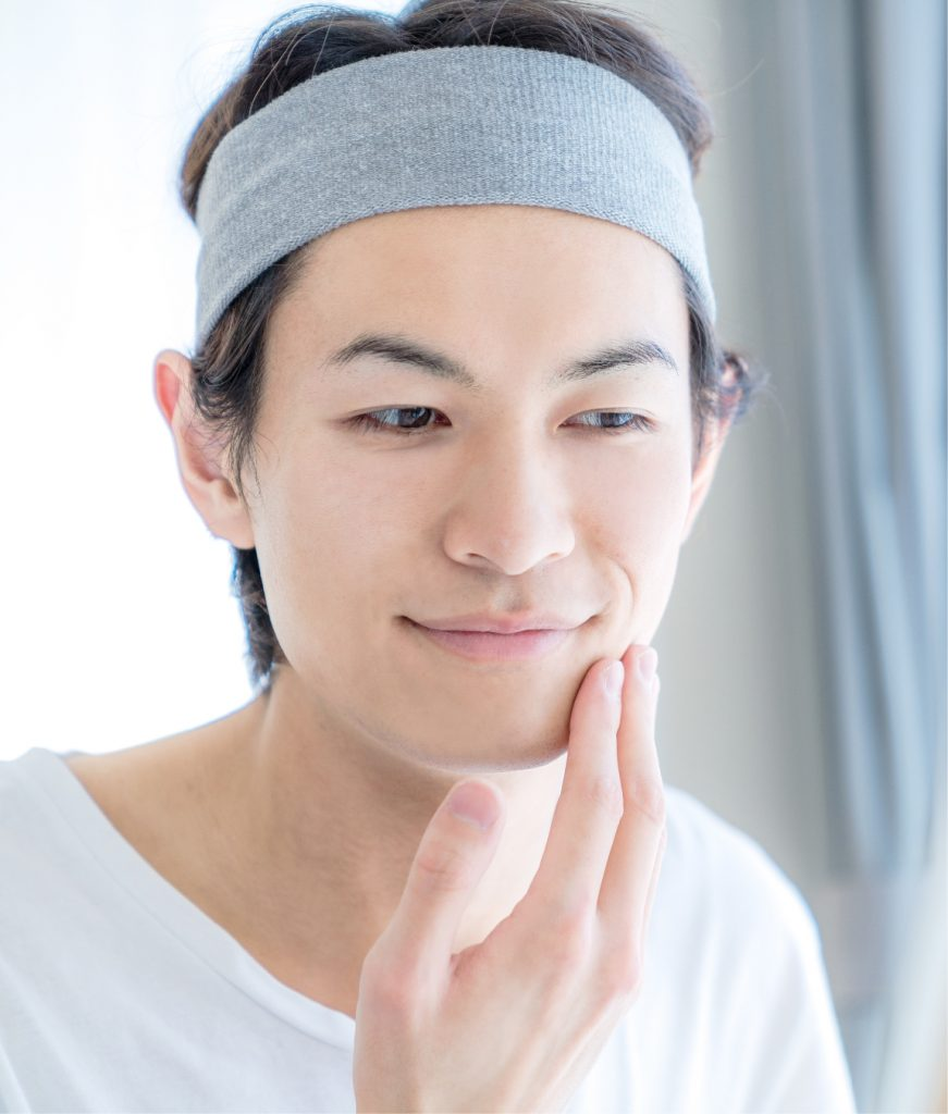 Man with good skin touching his face