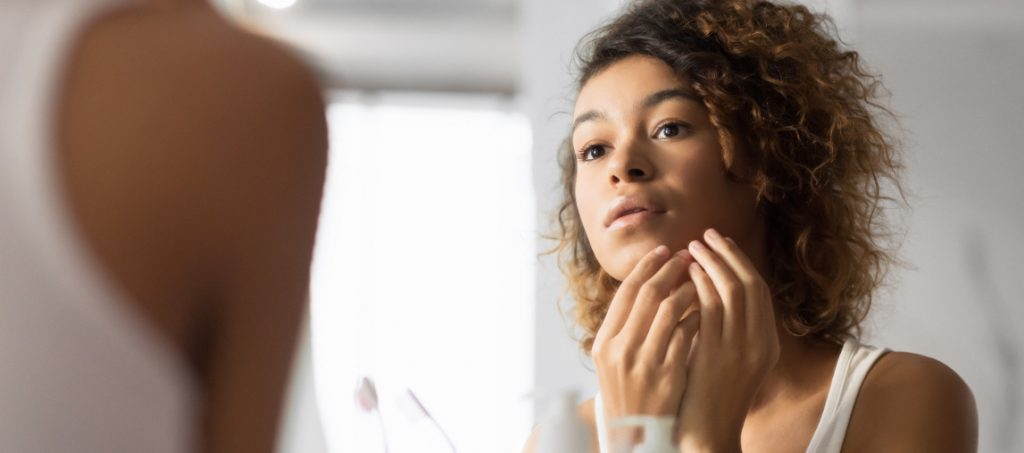 Young woman checking her skin for acne