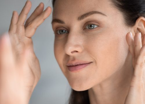 Woman looking at her face in the mirror after Bellafill treatments