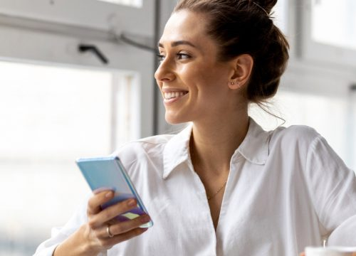 Smiling woman holding her cell phone, staring out the window of her apartment