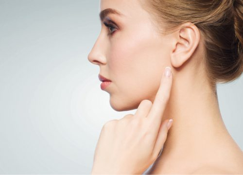 Woman pointing at her ear