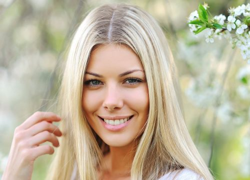 Blonde woman smiling outside surrounded by flowers