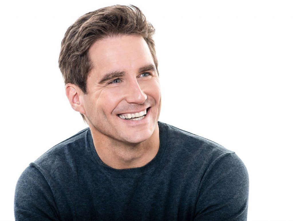 Man smiling, wearing a navy sweater