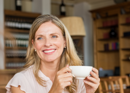 Older woman holding a coffee cup at a cafe